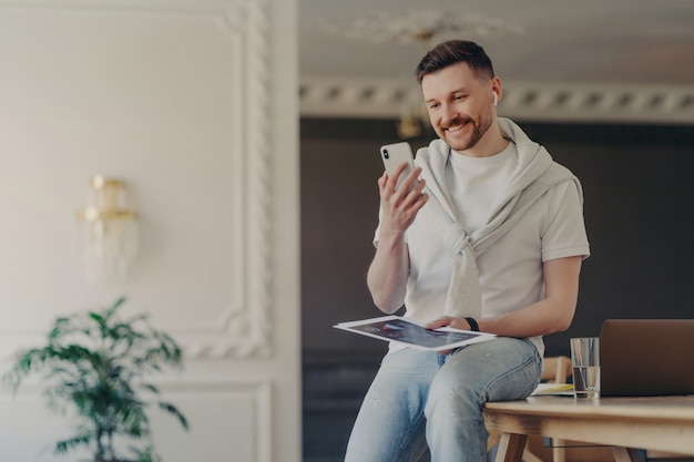Indoor shot of bearded adult man freelancer poses in coworking space makes video call via smartphone uses wireless earphones connected to free high speed internet has online conference with coworkers