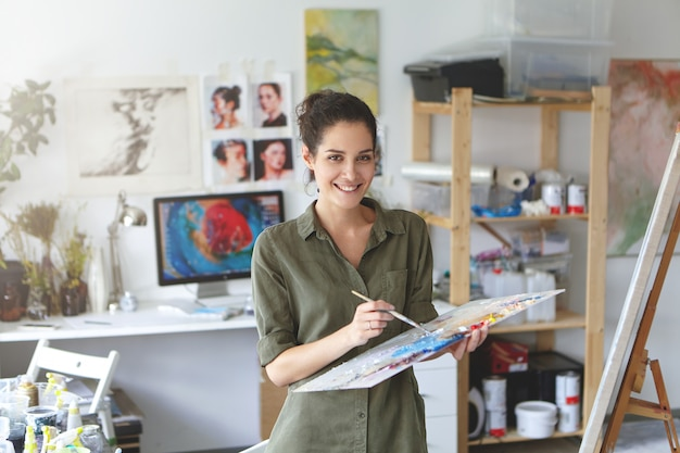 Indoor shot of beautiful brunette female painter wearing shirt, holding paint brush in hands standing near easel, creating masterpiece, smiling pleasantly while being glad to paint