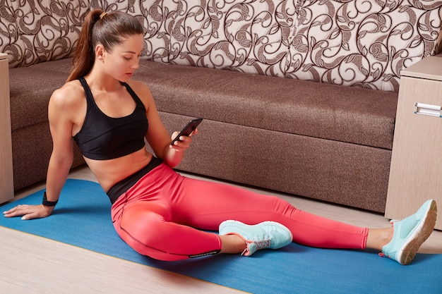 Indoor shot of beautiful caucasian sporty woman with smartphonein hands, doing exercise at home on yoga mat, lady dresses stylish black top and leggins, looking at device screen while sitting on floor