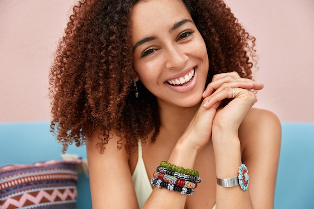 Indoor shot of beautiful dark skinned mixed race young female with afro hairstyle has pleasant smile, poses on sofa, wears bracelet, hears funny story from friend