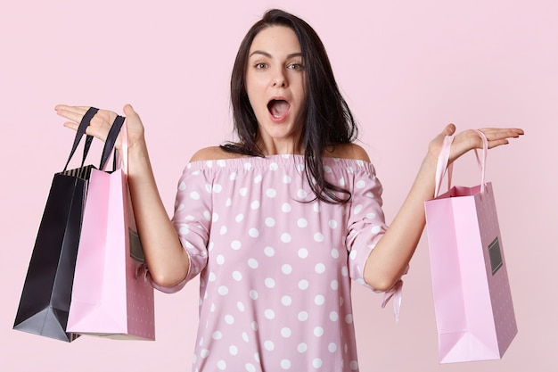 Indoor shot of beautiful fashionable caucasian woman holding shopping bags in both hands, has shocked facial expression