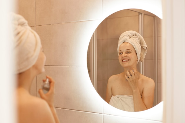 Indoor shot of beautiful girl in bath towel on her head using perfume while posing in bathroom, enjoying pleasant odor, looking at her reflection in the mirror.