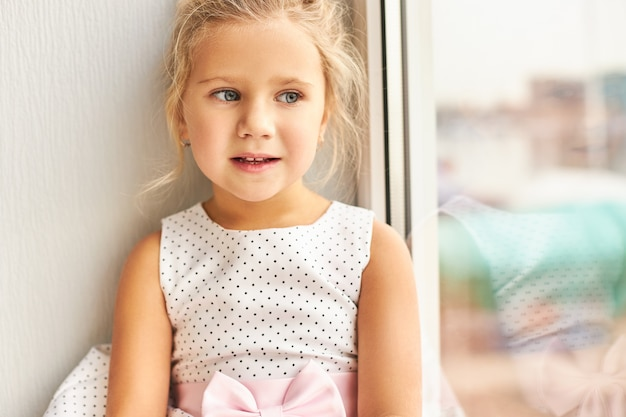 Indoor shot of beautiful sad caucasian girl in dotted dress sitting on windowsill, having upset look, feeling lonely, waiting for parents from work. people, children, lifestyle and loneliness concept