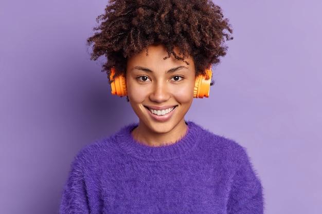 Tiro al coperto di bella ragazza adolescente sorride felicemente indossa cuffie stereo ascolta musica dalla playlist vestita di caldo maglione di cashmere pone