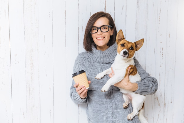Indoor shot of beautiful woman with short dark hair, wears square spectacles and grey winter sweater, holds hot beverage in hot paper and little dog