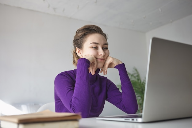 Indoor shot of beautiful young female in purple long sleeved top sitting at desk in front of open laptop, watching video blog