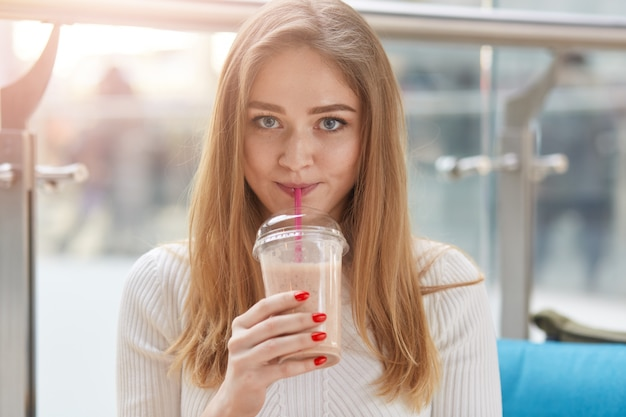 Indoor shot of beautiful young woman drinking milk cocktail