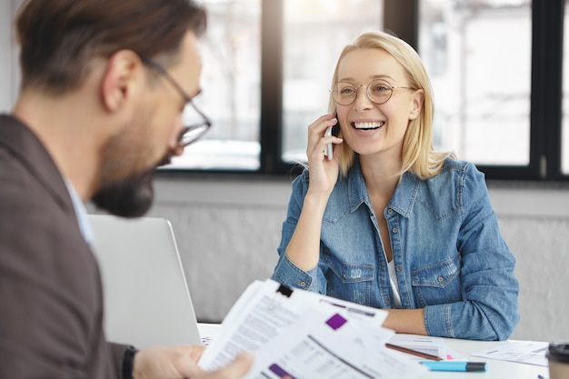 Indoor shot of blonde female having business conversation with colleague