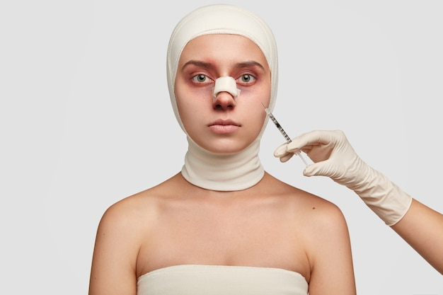 Indoor shot of bruised woman with pale skin, has plaster on nose, wrapped in bandages, recieves injection from surgeon, has serious facial expression.
