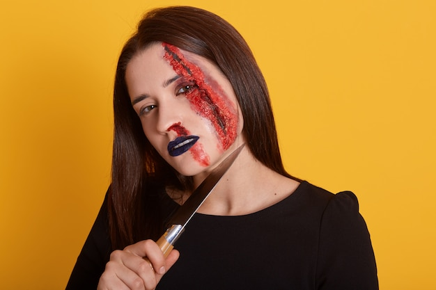 Indoor shot of brunette female with knife near her neck and bloody wound on her face