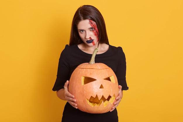 Indoor shot of brunette woman in halloween makeup holding pumpkin over yellow