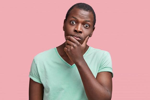 Tiro al coperto di bel maschio afroamericano con gli occhi infastiditi mantiene il mento e ascolta le informazioni con uno sguardo attento e scrupoloso