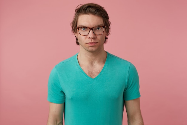 Indoor shot of calm young male, looks directly into camera with no emotions on his face, isolated over pink background