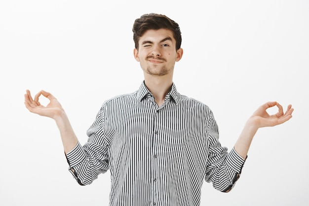 Indoor shot of carefree good-looking friendly guy with moustache in shirt, spread hands in zen gesture, peeking with one eye and smiling while watching students during practicing yoga or meditation