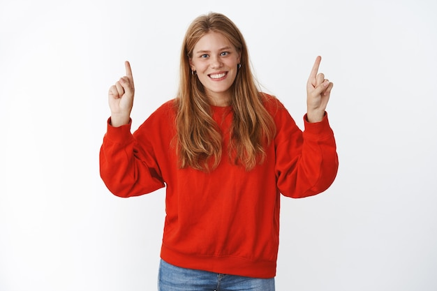 Indoor shot of carefree happy young charismatic fair-haired woman with freckles and blue eyes smiling sincere and happily standing in cute red oversized sweater pointing up with delighted expression