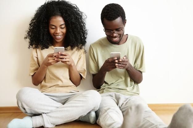 Tiro al coperto di giovane famiglia dalla carnagione scura vestita con indifferenza seduto al muro bianco bianco sul pavimento di legno con gadget, utilizzando app online