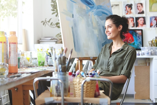 Indoor shot of charming cheerful young european female art teacher with dark curly hair and cute smile sitting at her workshop, surrounded with paints, brushes, waiting for students, looking inspired