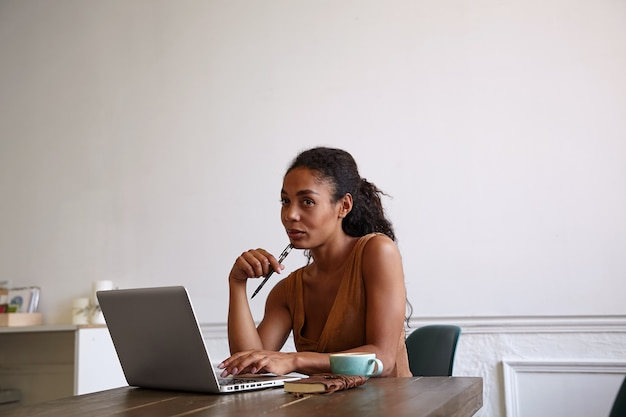 Indoor shot of charming dark skinned woman with casual hairstyle working with her laptop, looking opposite herself with soft smile, keeping pen on her chin