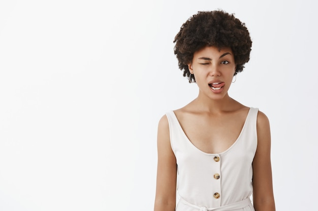 Indoor shot of charming flirty emotive african american woman with curly hairstyle sticking out tongue sensually and winking with hing, making romantic suggestion, expressing empathy over gray wall