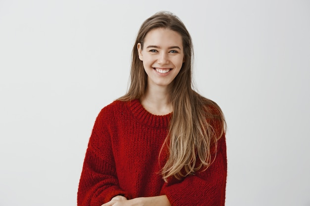 Indoor shot of charming friendly-looking european woman in stylish loose sweater, talking casually with coworker during break at work, smiling broadly, being charmed and excited with conversation
