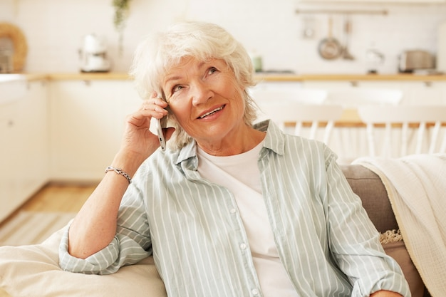 Indoor shot of charming friendly senior gray haired woman holding generic smart phone close to her ear, having hearing problem, talking to her friend, sitting comfortably on couch in living room