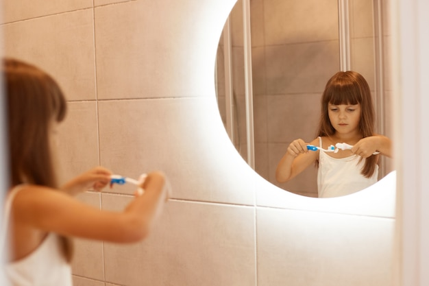 Indoor shot of charming little girl brushing teeth in bathroom, squeezing toothpaste out of a tube, standing in front of the mirror, having concentrated facial expression.