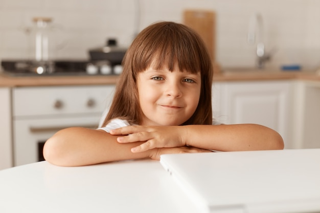Indoor shot of charming little preschooler girl with dark hair sitting at table with folded notebook, looking at camera, posing at home in light room with kitchen set on background.