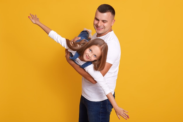 Indoor shot of cheerful awesome man lifting his kid