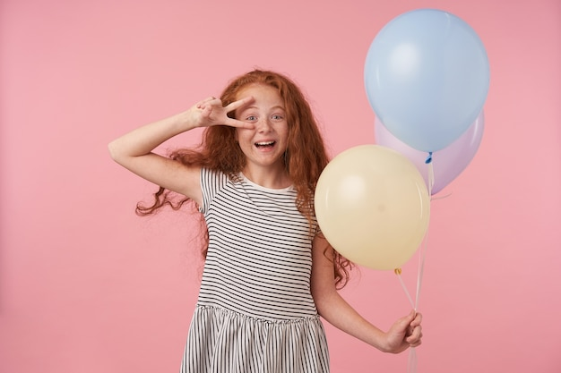 Indoor shot of cheerful curly girl with curly long hair wearing striped dress over pink background, holding colored air balloons in hand and smiling broadly to camera raising peace gesture to her face