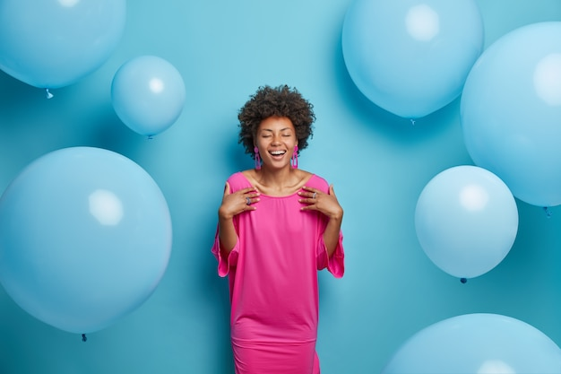 Indoor shot of cheerful curly woman in pink fashionable dress, closes eyes, prepares for speical occasion, glad to recieve congratulations with birthday, isolated on blue backgroud, inflated balloons