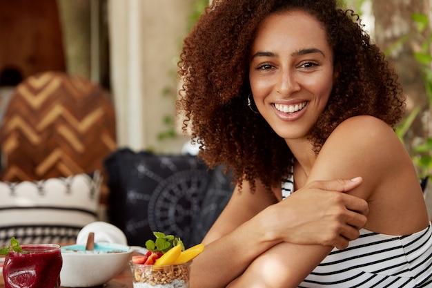 Tiro al coperto di giovane donna afroamericana dalla pelle scura allegra con sguardo felice, trascorre il tempo libero in buona compagnia, si siede contro l'interno della caffetteria, mangia deliziosi dessert. concetto di ricreazione