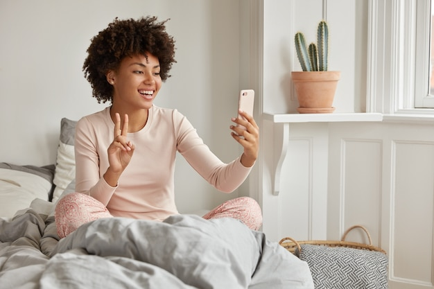Indoor shot of cheerful dark skinned woman dressed in casual pyjamas, has morning video call, holds modern mobile phone, poses on bed, smiles broadly, shows peace sign at screen. selfie in morning