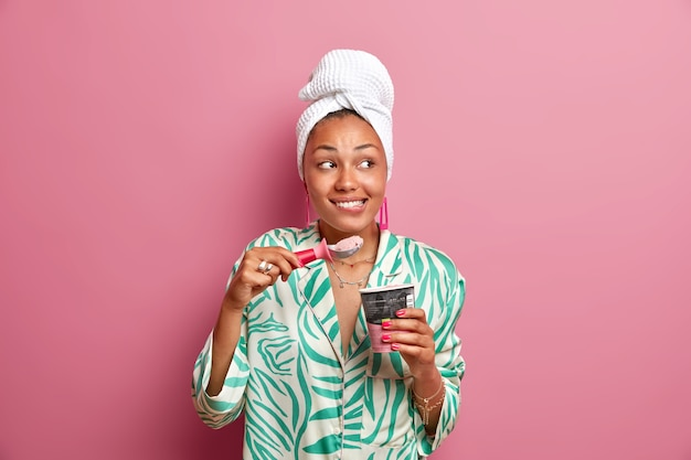 Colpo al coperto di allegra giovane donna dalla pelle scura che morde le labbra si diverte a mangiare appetitoso gelato freddo dal cucchiaio trascorre il tempo libero a casa vestita con abiti casual isolati sul muro rosa