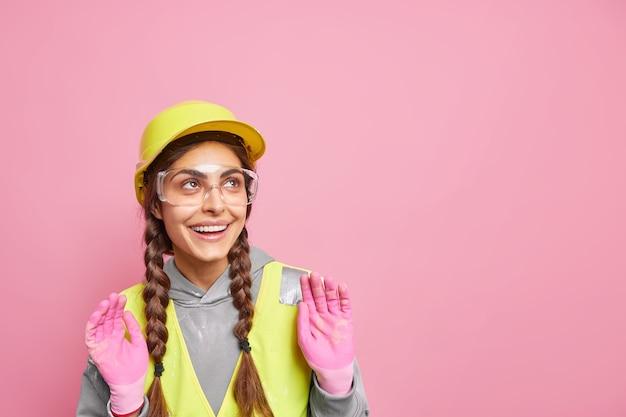 Indoor shot of cheerful female maintenance worker keeps hands raised looks somewhere