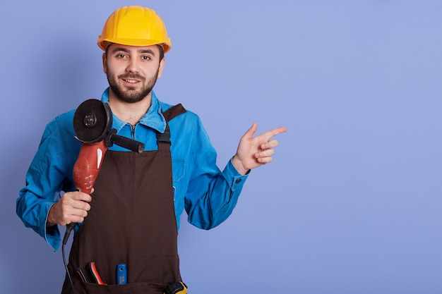 Indoor shot of cheerful handsome positive builder, smiling sincerely, holding angle grinder in one hand, making gesture, showing gesture. copyspace for advertisement.