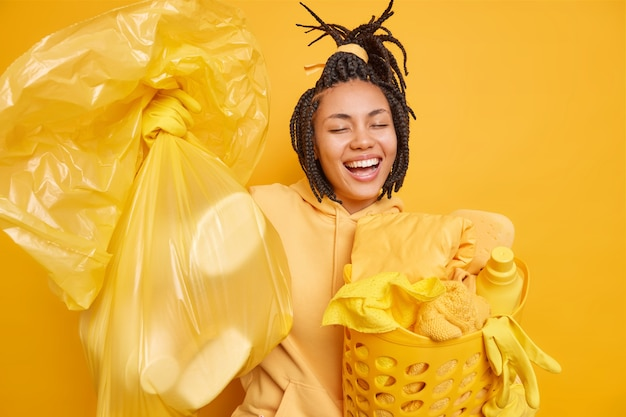 Indoor shot of cheerful housemaid laughs happily carries polythene bag full of trash does laundry involved in housework expresses positive emotions isolated on yellow