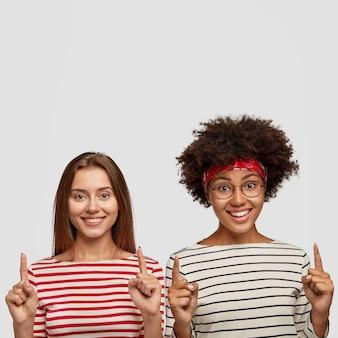 Tiro al coperto di donne multietniche allegre con sorrisi teneri e affascinanti, pubblicizzare un nuovo oggetto, puntare con entrambi gli indici verso l'alto