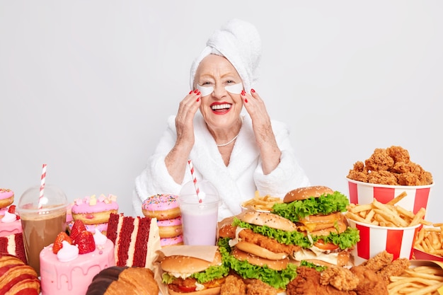 Indoor shot of cheerful old lady applies patches under eyes to reduce wrinkles has red manicure smiles broadly being in good mood eats big portions of fast food