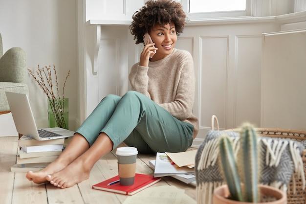 Indoor shot of cheerful satisfied dark skinned businesswoman or entrepreneur works on creating new plan