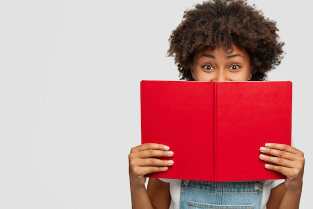 Indoor shot of of cheerful woman covers face with red textbook, has joyful expression
