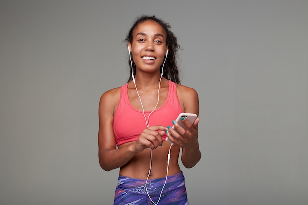 Indoor shot of cheerul young sporty dark haired curly female with casual hairstyle holding mobile phone in hands and weaing headphones while looking positively