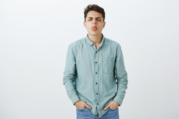 Indoor shot of childish displeased european guy in casual outfit
