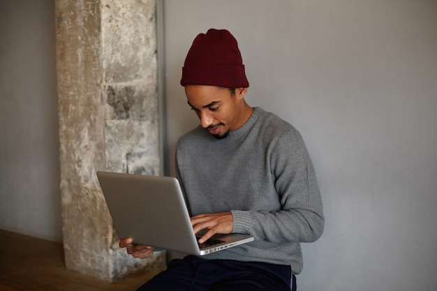 Indoor shot of concentrated lovely dark skinned guy with beard, holding laptop and looking on screen with thoughtful face, sitting over white wall in casual clothes