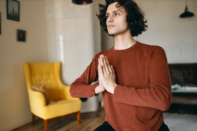 Indoor shot of concentrated young male in casual clothes holding hands pressed together while meditating at home during yoga practice, focusing attention on positive thoughts.