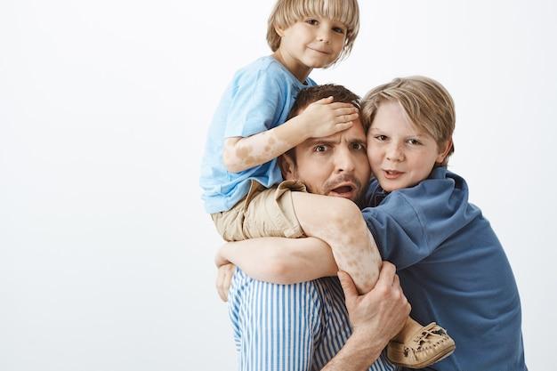 Tiro al coperto di padre stanco preoccupato che tiene carino figlio biondo con vitiligine sulle spalle, accigliato e preoccupato mentre il fratello maggiore è appeso al petto di papà