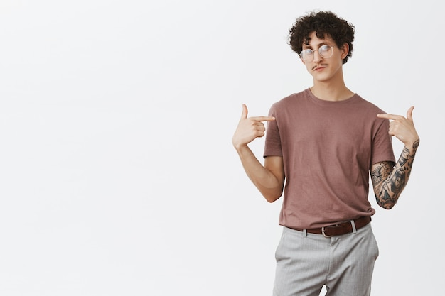 Indoor shot of confident artistic and creative jewish guy with dark curly hair and moustache standing in self-assured pose pointing at himself proudly presenting himself as perfect candidate
