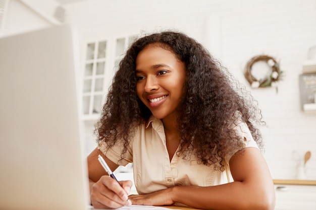 Indoor shot of confident cheerful young dark skinned female freelancer sitting at dining table, working remotely using portable computer. modern electronic gadgets, job and occupation concept