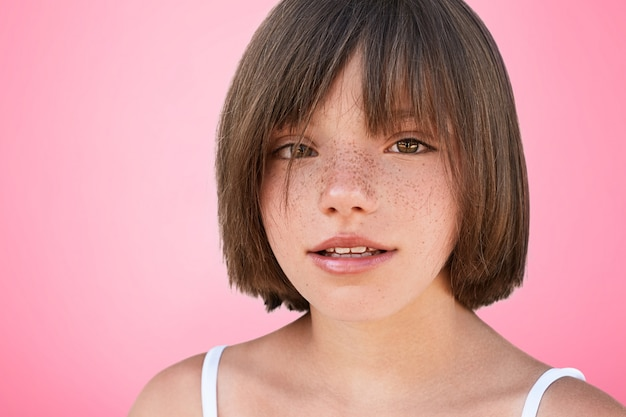 Indoor shot of confident freckled beautiful small female child with bobbed hairstyle looks at camera, glad to be photographed in studio, poses on pink. little kid looks at you