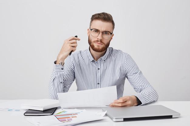 Tiro al coperto di capo o datore di lavoro maschio giovane rigoroso fiducioso, ha barba e acconciatura alla moda