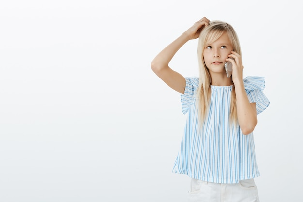 Indoor shot of confused questioned adorable female child with blond hair in blue blouse, scratching head and looking up while talking on smartphone, thinking what she wants to order from granny